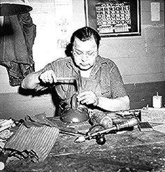 Kidd Smith, Seneca carver, at work in the Tonawanda Community House. Photographed by Helen Post, 1940.