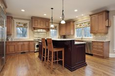 A spacious kitchen with light wood cabinets and a large, dark wood island with raised dining area.