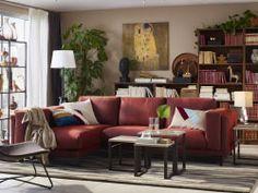 3人掛けの錆色レッドのソファコンビネーションを置いたリビングルーム。3つのネストテーブルと天然繊維のダークブラウンのアームチェア