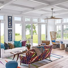 Light and bright open-plan living room with wooden floor, striped rug and bold print sofa
