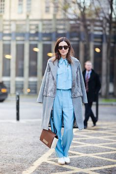 Contrasting sky blue look with a grey coat and a rich caramel brown purse