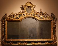 Espejo de una cómoda quizás lombarda, specchiera, 1700-50 ca. Pese a lo recargado de la talla, aún es simétrica, característica que se perderá en el periodo Rococó.