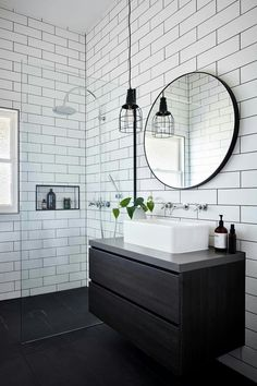 Bathroom White subway tiles are laid horizontally in this smaller bathroom, with the same large format black tiles on the floor. A circular mirror sits above a white basin and black timber vanity, with an industrial-style pendant lamp hangs above. Bathroom Renos, Bathroom Flooring, Bathroom Tray, Gold Bathroom, Round Mirror In Bathroom, Bathroom Lamps, Black Vanity Bathroom, Bathroom Accents, Bathroom Basin