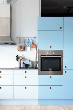 Reform Basis 01 kitchen in two light blue colors, handles in natural oak and a table top in Charcoal linoleum on IKEA elements.