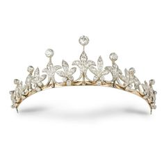 A LATE VICTORIAN DIAMOND TIARA --  1890,  the tiara comprising nine graduated diamond-set fleur de lys motifs with old brilliant-cut diamond tops, alternating with graduating diamond set leaf motifs with diamond trefoils to bottom, all to a gold frame with diamond set scalloped knife edge necklet back, diamonds estimated to weigh a total of 15 carats, set in silver to a yellow gold mount