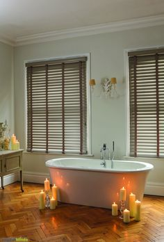 Light brown taped wooden blinds in a contemporary bathroom with a roll top freestanding bath.