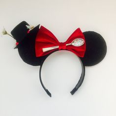 These ears, in a word are, Supercalifragilisticexpialidocious! These Mary Poppin inspired ears are made with a very glittery black and white foam trimmed in black sequin. Red velvet bow tie, with a silver soon, and sugar, of corse! (Glitter) Black satin covered headband. The back has an umbrella, and a quote. Most importantly, it comes with her hat complete with berries and flowers! The hat measures 3 inches. This is a show stopper!! (Please note that flowers and lettering will vary slightly…
