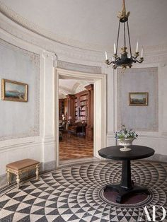 Paved with a Roman-inspired mosaic, the elliptical entrance hall of a Naples, Italy, apartment designed by Studio Peregalli features 18th-century paintings by Pietro Antoniani as well as a Louis XVI stool; the French Empire chandelier is suspended above an antique English lavastone pedestal table   archdigest.com