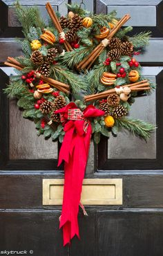 Winter Wreath dried orange slices whole cinnamon pinecones berries and lemons on fresh greenery. . .