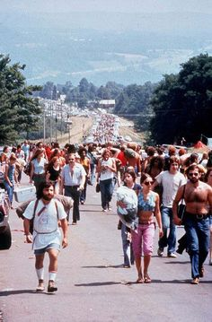 August 1969, Crowds of people carry picnic and camping supplies while walking past parked cars on the road to the Woodstock Music Festival in Bethel, New York.
