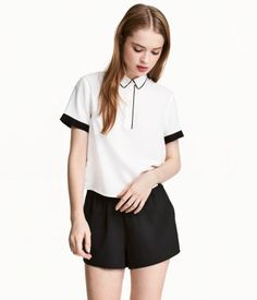 White. Short-sleeved blouse in woven viscose fabric with contrasting details. Collar, button placket, and yoke at back with pleat. Straight-cut hem with
