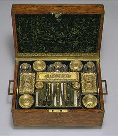 A William IV silver-gilt travelling toilet set, Charles Rawlings and William Summers, retailed by Edwards, 1832 comprising the following with silver-gilt covers, chased borders of oak, engine-turned and inset with monogrammed gold roundels: three cut-glass Boxes, six cut-glass Jars including two with screw covers, three Bottles; two gold-mounted Scent Flasks (one with chipped neck); tray of manicure instruments in gold-decorated steel including two folding knives, two pairs of scissors, and…
