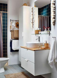 Ein kleines weißes Badezimmer mit GODMORGON/ALDERN Waschbeckenschrank mit Aufsatzwaschbecken in Weiß/Bambus, GODMORGON Hochschrank in Weiß und Zubehör in Bambus.