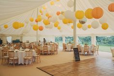 To create a fresh marquee look with coloured hanging lanterns mix sunshine yellow with white and peach paper lanterns
