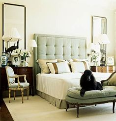 Blue tufted headboard with black poodle