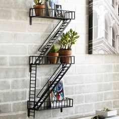 Wall art that doubles as storage? Sure, why not! Epoxy-coated steel has been welded by hand to create this hanging industrial shelving piece. Imitating the familiar form of a fire escape, some of its adjustable shelves can hang down like ladders while others display plants, books, pictures, and more.