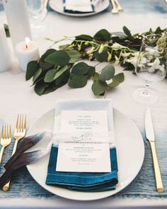 A Boho Wedding on a Private Island in Connecticut | Martha Stewart Weddings - Tables were set with gold flatware and simple white plates. Menus sat atop dip-dyed napkins, tied together with either leather cord or monogrammed silk ribbons. With a mix of tables, the arrangements also differed, varying between low planters of white and blue flowers, all greenery (like ruscus, bay leaves, and olive branches), and small white vases with single blooms.