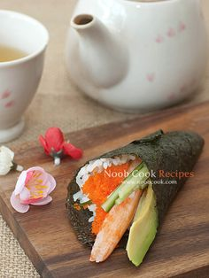 """California temaki - avocado, cucumber, crab sticks and ebiko (prawn roe) カリフォルニア手巻き Temaki (手巻, """"hand rolls"""") is a cone-shaped piece of nori (seaweed) on the outside with the rice and fillings spilling out the wide end. One of my favourite temaki is the California temaki"""