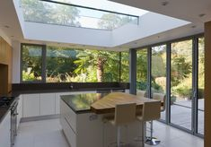 A modern kitchen extension with structurally glazed wrap around windows and bifold aluminium doors and a central island breakfast bar