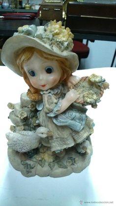Figura de niña con sombrero.