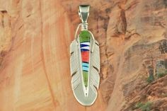 Genuine Turquoise, Spiny Oyster Shell, Magnesite and Blue Lapis inlaid in Sterling Silver. Feather Pendant Designed by Navajo Artist Calvin Begay. $148.00