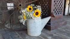 Sunflowers and baby's breath in a vintage watering can. Perfect for a country wedding!