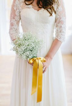 Bride Carries A Pretty Bouquet Of White Gypsophila (Baby's Breath) Hand Tied With A Gold Satin Ribbon