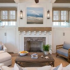 Brick hearth with white trim. Wood mantel supported by several small white corbels. Two lights framing the seascape photo seem like lanterns and really make it feel like the outdoors beach. Sisal or wicker-like fabric window shades.