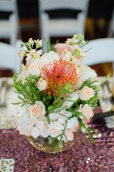 A low centerpiece featuring blush and coral florals sat atop a pink sequin runner. #BridalShower Photography: EDLT Photo. Read More: http://www.insideweddings.com/weddings/modern-spring-bridal-shower-with-a-pink-gold-black-color-palette/640/