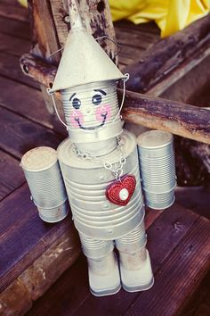 Decorate your entryway with this super cute DIY tin man (with a heart!) using a funnel, various aluminum cans, and silver spray paint!