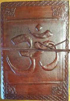 This blank leather journal has a centered tooled embossed Om adorned on its front cover, with Celtic designed border edging. It displays a large centered tooled embossed, encircled lotus on its back c