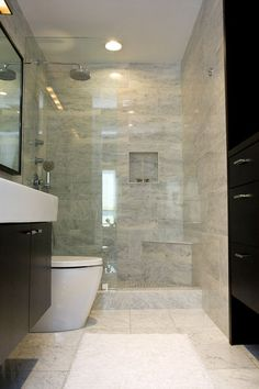 Attached to the family and media room is a bathroom with a clean, simple aesthetic. A standard European shower finishes the space.
