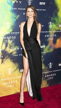 Model and VS Angel, Behati Prinsloo in a floor length black dress with a deep V neckline and sexy high slit