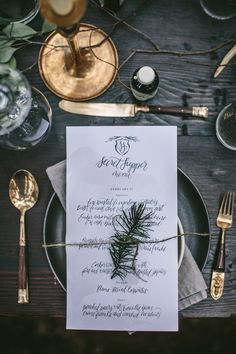 Hand lettered menus with taupe watercolor washes and a simple pine crest