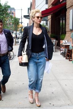 The epitome of casual-cool (pefectly mussed bun and all), Lawrence styles a boyfriend blazer over a black tank and slouchy boyfriend jeans. Both practical and chic, she dons a pair of studded wedge sandals, as well. - MarieClaire.com