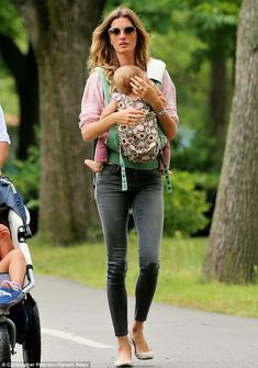 Hometime: Gisele cradles baby Vivian in a sling as the family make their way home