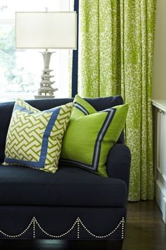 Pattern on sofa skirt!  Trim on pillows. Unusual lamp.  Green curtains!  Attention to detail....