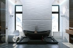 salle de bain moderne en noir et blanc avec une baignoire îlot noire, une chaise blanche de design ovale et une déco murale blanche en relief