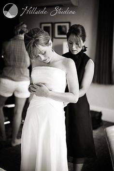 Serene image of bride having dress laced by her sister and maid of honor. I love this shot.