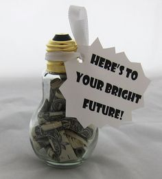 "Light Bulb Money Holder Brighten your grad's day with this unexpected presentation. Roll up the dollar bills then fold them in half (to prevent them from unrolling inside of the jar). Place them in this light bulb jar from Hobby Lobby and tighten the screw cap lid. Attach a ribbon with a cute phrase like ""Here's to your bright future."" (Tip: If the dollar bills are stuffed tight inside the jar, suggest he/she use tweezers to remove them later on).  Light Bulb Money Holder"