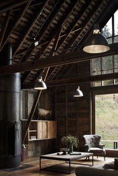 big windows, loft, exposed beams, and hanging pendants lamps turn moody colors into a comfortable warm place