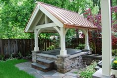nice hot tub pavilion with stacked-stone surround and standing-seam copper roof