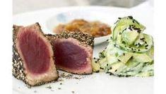 1 Thunfischsteaks mit Salz und grobem Pfeffer würzen, den Pfeffer dabei fest andrücken. Das Sonnenblumenöl in einer großen Pfanne erhitzen und die Steaks darin von jeder Seite 1 - 2 Minuten braten. Dabei vorsichtig wenden, damit der Pfeffer nicht abfällt. Tunfisch schmeckt am besten, wenn er in der Mitte noch roh ist.   2 Avocados schälen und entkernen. Fruchtfleisch in Würfel schneiden. Die Gurke unter heißem Wasser waschen und in dünne Scheiben schneiden. Gurkenscheiben und Avocadowürfel…