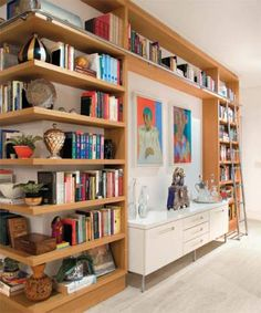 Prateleiras até o teto compõem a biblioteca deste apartamento, decorado pel...