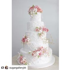 Five- tiered White wedding cake with white scroll designs inlayed on each layers with pink & white floral flowers.
