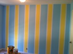 How to paint 3 stripes:  1. Sample colors and pick 3 that will complement each other.   2. Figure out the dimensions of the room and stripes width. My wall was 11 feet long. I chose 12 inch blue stripes, 6 inch yellow stripes, and 2 inch white stripes.   3. Paint the entire wall with the lightest color (the tape will cover this.)   4. Make your measurements, placing the tape exactly where you want it.   5. Seal the tape using a credit card.   6. Paint.  7. Remove tape about an hour later.