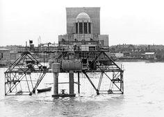 1942. Het stalenframe op de tunnelbuis met in het midden de duikersklok en links de compressor.. Voor het werk aan de naden, was een lange tunnelvormige stalenduikersklok op de tunnel geplaatst die met zware gewichten op de tunnel werden gedrukt. Door de druk in de klok te verhogen naar 2,7 atmosfeer was er een droge omgeving waar de coisson arbeiders de naden konden dichten. Werkruimte 1 meter!. Rechts ecompressieklok en links de compressor.