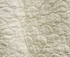 """Hand-quilted cotton petticoat, late 18th century.This petticoat was purchased from a New England collection. The oral provenance is that the petticoat came from New Hampshire or Massachusetts. The body of the petticoat is quilted with a shell pattern. The hem border has undulating feathers surrounded by diagonal rows. The border is outlined with rows of corded trapunto. The quilting is finely executed with 10-12 stitches per inch.The petticoat is 39"""" long and a 91"""" bottom circumference"""