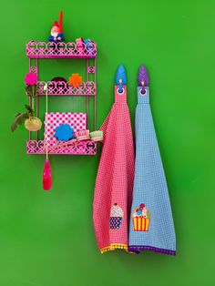 RICE Kitchen rack, tea towels and flamingo hooks hanging on green wall