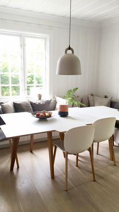 Scandinavian home kitchen featuring RBM Noor chairs in vanilla with wooden oak legs. RBM Twisted Little Star tables with oak legs in nature. Normann Copenhagen Bell lamp. #rbmnoor #homedecor #kitchendesign #kitchendecor